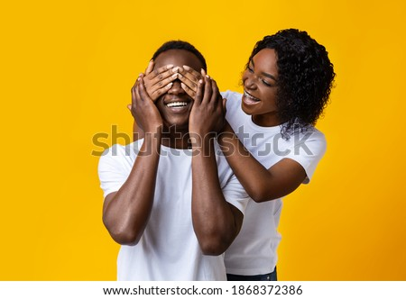 Portrait of happy covers eyes to her husband, prepares surprise for him, wears casual red oversized  Stock photo © vkstudio