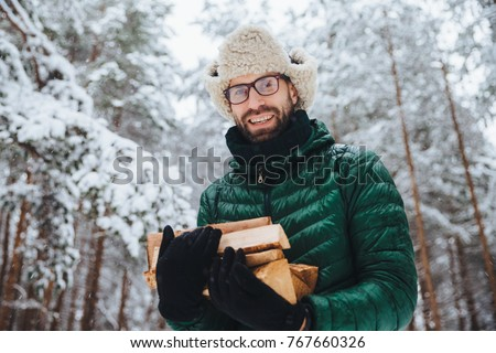 Handsome bearded male in eyewear and warm hat with anorak, holds firewood, poses against trees cover Stock photo © vkstudio