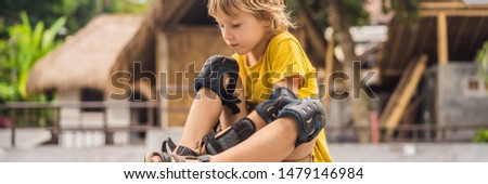 Boy puts on knee pads and armbands before training skate board BANNER, LONG FORMAT Stock photo © galitskaya