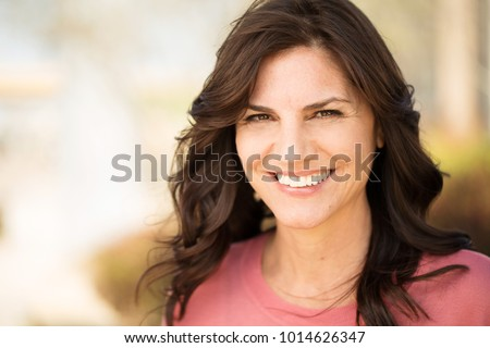 Smiling happy mixed race woman enjoying serene sunset. Carefree Asian woman relaxing on beach travel Stock photo © Maridav