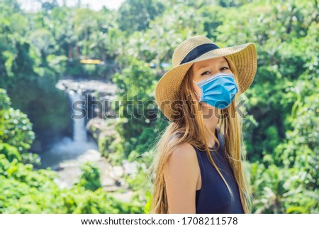 Woman in medical mask traveler on a waterfall background. Ecotourism concept Tourists fear the 2019- Stock photo © galitskaya