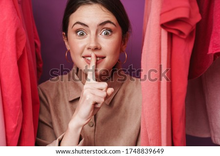 Photo of woman making silence gesture while standing at clothes rack Stock photo © deandrobot