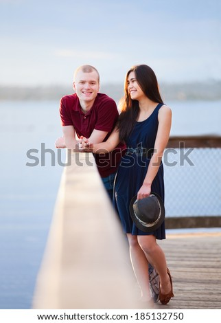 young interracial couple standing together on wooden pier overlo stock photo © jarenwicklund