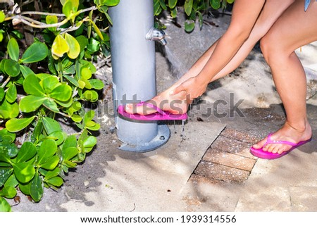 Woman rinsing of at the beach under a shower Stock photo © d13
