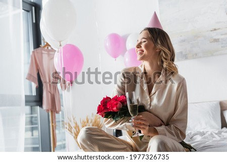 Smiling Woman in Sleepwear Holding a Rose Bouquet Stock photo © dash