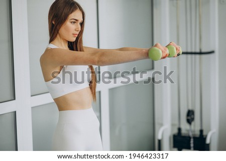 attractive young sportswoman working out with dumbbells in gym stock photo © deandrobot