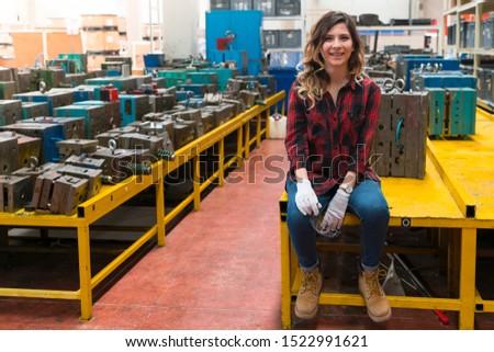 Female mechanic sitting in metal workshop looking into camera Stock photo © Kzenon