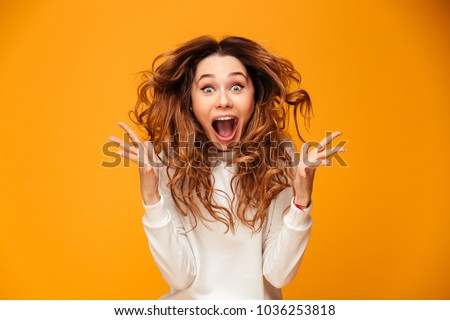 Excited young cute woman posing isolated over yellow background. Stock photo © deandrobot