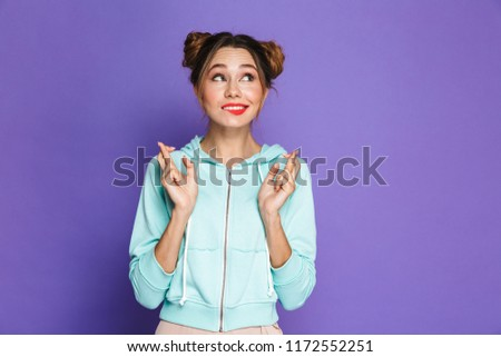 portrait of funny young girl with two buns keeping fingers cross stock photo © deandrobot