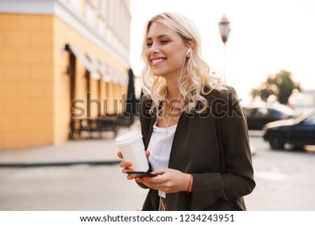 Image of blonde woman wearing earphones holding takeaway coffee  Stock photo © deandrobot