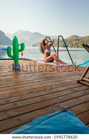 fiatal · nő · bikini · ül · móló · tó · hátulnézet - stock fotó © boggy