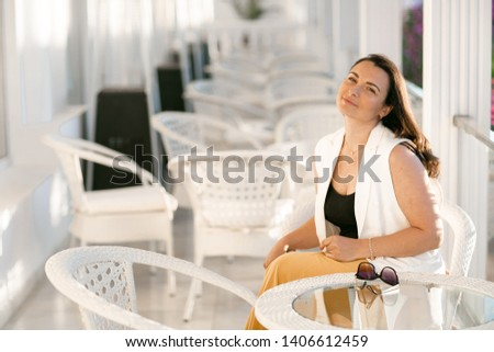 A Moderately obese businesswoman sitting in a cafe while holding coffee Stock photo © ElenaBatkova