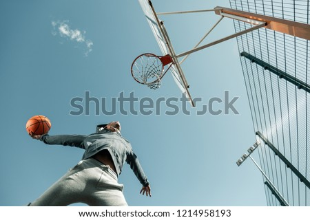Young active basketball player throwing ball while exercising on playground Stock photo © pressmaster