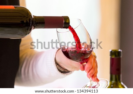 Waitress pouring red wine in wine glass on table in restaurant Stock photo © wavebreak_media