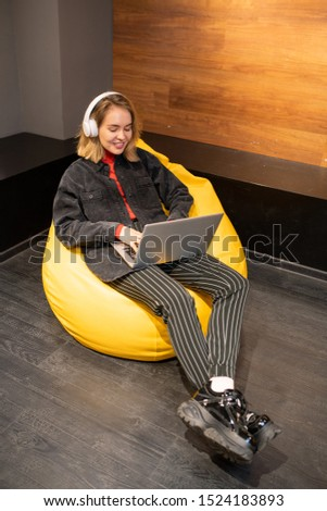 happy blonde girl sitting in soft comfy yellow leather armchair and relaxing stock photo © pressmaster