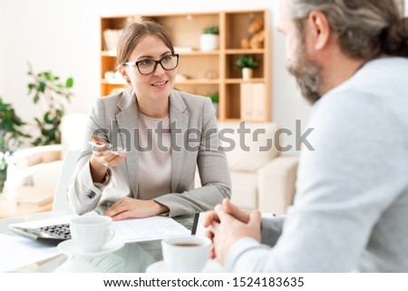 Happy accountant in formalwear looking at mature colleague during discussion Stock photo © pressmaster