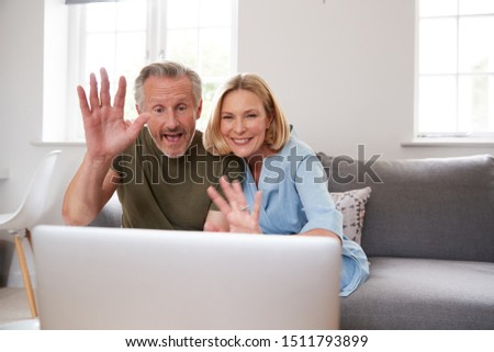 Front view of senior couple making video call on laptop in living room at home Stock photo © wavebreak_media