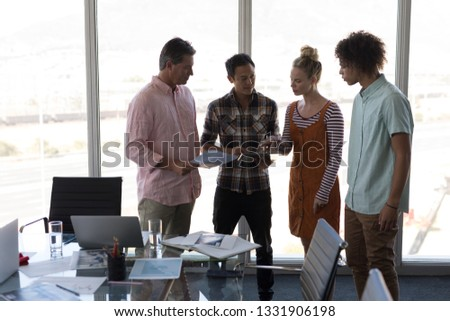 Front view of young multi-ethnic colleagues discussing business strategy over laptop in modern offic Stock photo © wavebreak_media