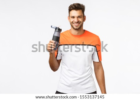 Fitness trainer remind you drink water. Handsome smiling, cheerful sportsman in activewear, finish m Stock photo © benzoix