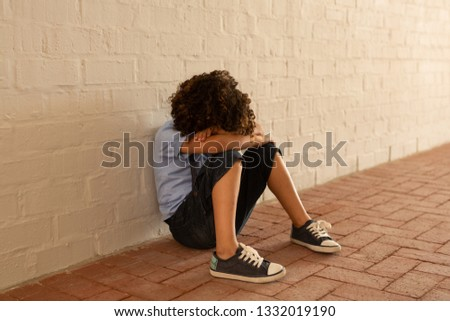 Side view of a schoolgirl sitting alone in school corridor while others school kids looking at her i Stock photo © wavebreak_media