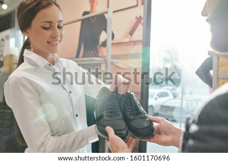 Happy young shop assistant showing pair of stylish warm sneakers to male buyer Stock photo © pressmaster