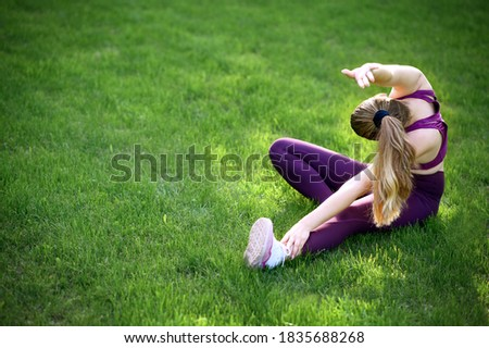 Delighted young athletic girl does stretching exercises, prepares muscles before training, dressed i Stock photo © vkstudio