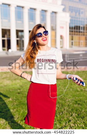 Image of brunette woman in red skirt smiling and holding smartph Stock photo © deandrobot