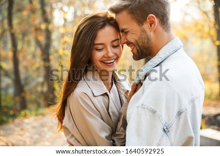 Image of attractive young caucasian couple walking through autum Stock photo © deandrobot