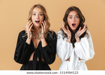 Portrait of cute women looking at camera and throwing up hands Stock photo © deandrobot