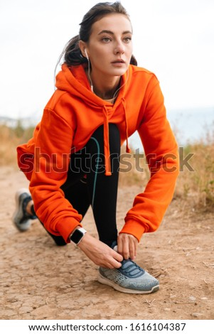 Photo of nice athletic woman using earphones and tying her shoelaces Stock photo © deandrobot