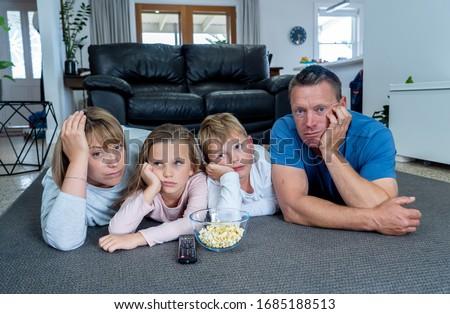 Coronavirus lockdow. Bored family watching tv helpless in isolation at home during quarantine COVID  Stock photo © galitskaya