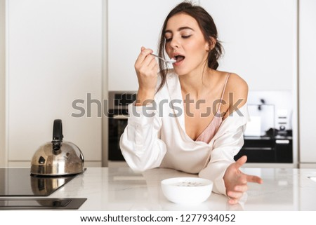 Photo of young smiling cute woman eating granola while having breakfast Stock photo © deandrobot