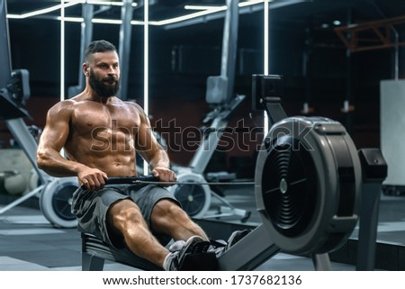 Fitness man exercising body on low pulley cable machine tower. Intense arm strength training workout Stock photo © Maridav