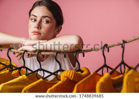 Photo of sad thinking woman looking aside while leaning on clothes rack Stock photo © deandrobot