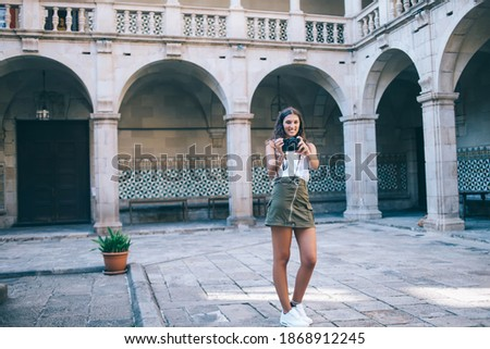 Photo of delighted woman smiling while standing at clothes rack Stock photo © deandrobot