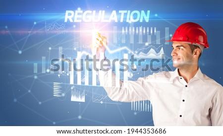 Young businessman with helmet drawing on virutal screen Stock photo © ra2studio