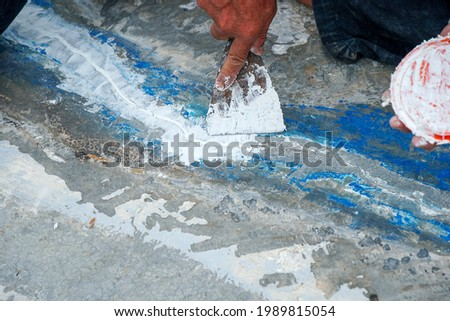 Stock photo: Roofer spreading cement