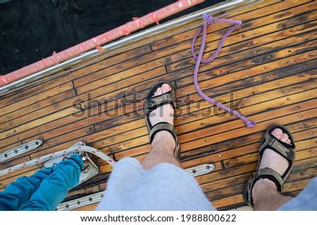 boat bow man feet blue sea view stock photo © lunamarina