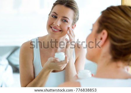 portrait of a young caucasian woman applying moisturizing lotion on the body Stock photo © ambro