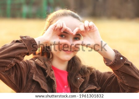 happy woman standing and looking through her fingers in park stock photo © deandrobot