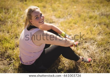 Portrait of happy woman relaxing on grass during obstacle course Stock photo © wavebreak_media