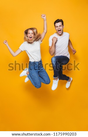 young man jumping isolated over yellow wall background using laptop computer stock photo © deandrobot