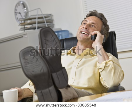 attractive business man leaning back in chair with legs on desk while chatting on the phone stock photo © minervastock