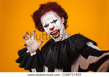 Shocking clown man 20s wearing black costume and halloween makeu Stock photo © deandrobot