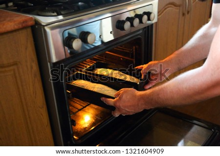 Man taking baked loafs of bread out of the oven. Beaking bread a Stock photo © dashapetrenko