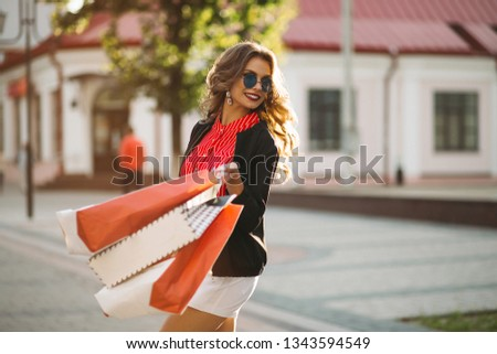 Positive woman  walking at street after shopping with many paper bags. Stock photo © studiolucky