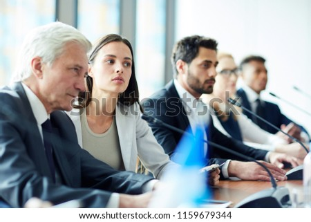 Mature elegant female delegate in suit speaking in microphone Stock photo © pressmaster