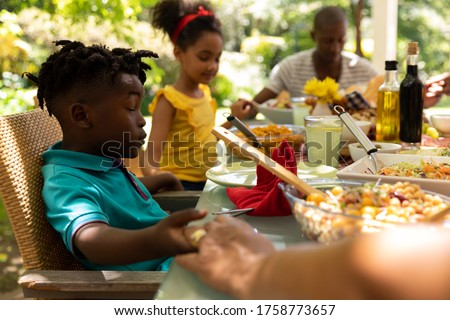 Side view of a multi-generation family praying together before having meal on dining table at home Stock photo © wavebreak_media