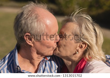 front view of active senior caucasian couple kissing each other in the park stock photo © wavebreak_media