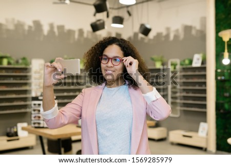 Smiling mixed-race girl in casualwear making selfie while trying on eyeglasses Stock photo © pressmaster